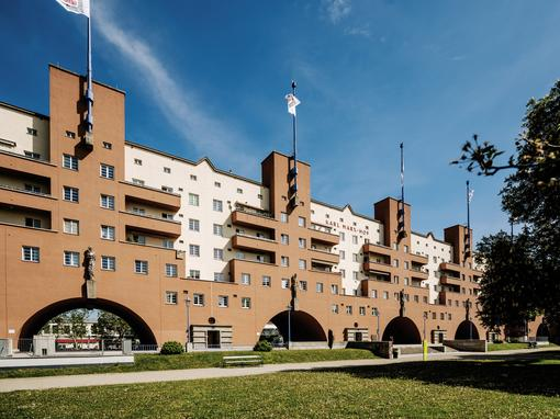 Photo of the Karl Marx Courtyard, an elongated building symetrically structured by arches, balconies and towers with flagpoles