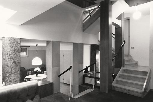 Black and white photo of a modern living room on two levels connected by stairs