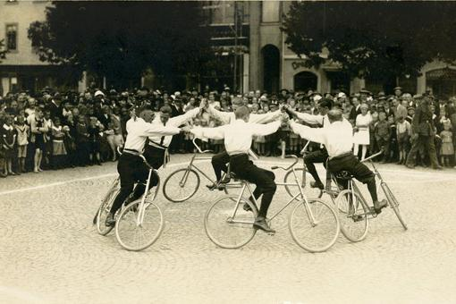 Black and white photo with a formation of 6 cyclists holding hands