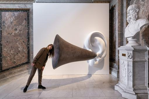 Photo of installation of an oversized ear trumpet from a white ear on a white wall