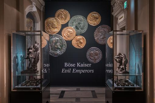 Exhibition view in the Kunsthistorisches Museum / Coin Cabinet, showcases with coins and statues