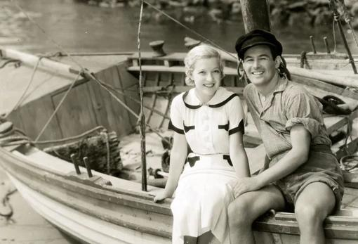 Black and white photo of Marta Eggerth and Jan Kiepura sitting on a wooden sailing ship lying on the beach