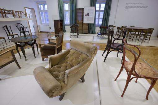 Photo with historical chairs, in the foreground a light brown armchair