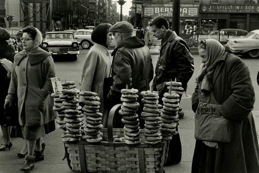 Black and white photo: Street scene with different people, in the foreground an old woman selling bagels at a mobile stand