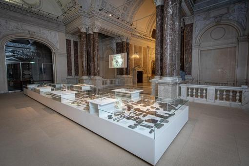 Exhibition view: white showcase with numerous objects and glass plate, in the background marble columns