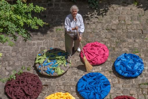 The artist in a light-grey blouse and pants holds a broom in her hand to create circular, colorful fabric and yarn objects