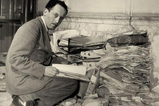 Black and white photo with a man in a suit, squatting and a file on his knees, in the background a mountain of files and folders