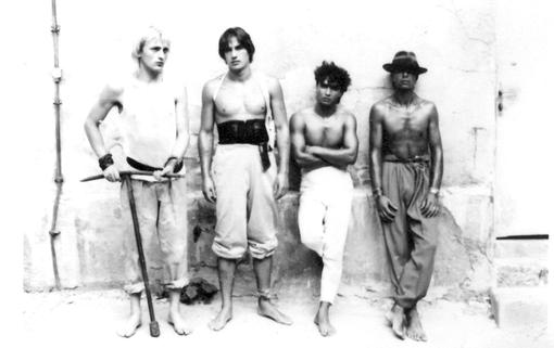 Black and white photo with four young men with naked upper body in front of a bright wall